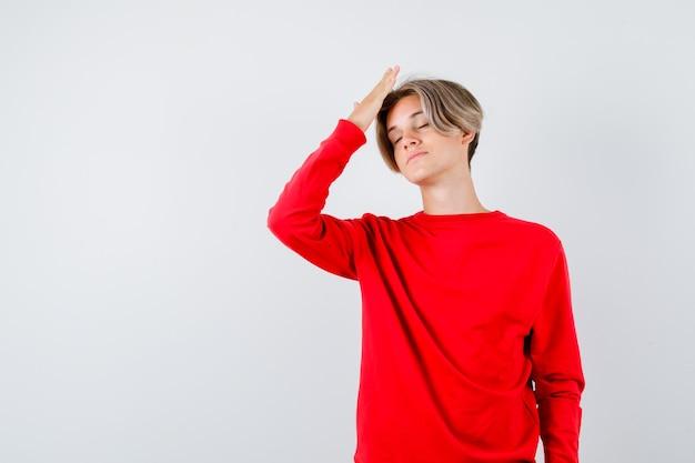 Portret nastoletniego chłopca trzymającego rękę nad głową, zamykającego oczy w czerwonym swetrze i patrzącego na zmęczonego widoku z przodu