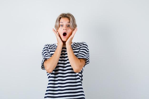 Portret nastoletniego chłopca z rękami na policzkach, otwierającymi usta w koszulce i przerażonym widokiem z przodu