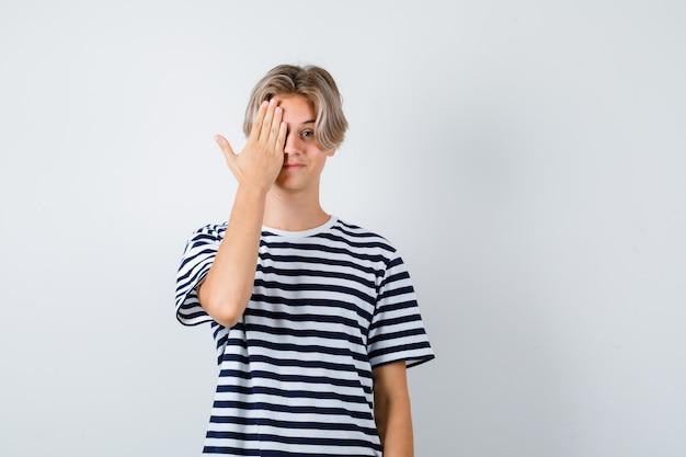 Portret nastoletniego chłopca zakrywającego oko ręką w koszulce i patrzącego na pozytywny widok z przodu