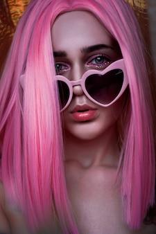 Portret nastoletniego modelu z różowymi włosami. funky nastolatek nosi kolorową perukę i modne okulary. pionowe zdjęcie - dobry format dla opowiadań