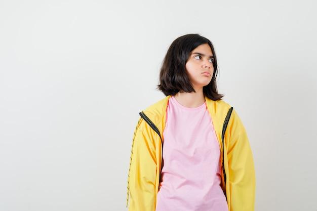 Portret nastoletniej dziewczyny patrzącej na bok w t-shirt, kurtce i zainteresowanym widokiem z przodu