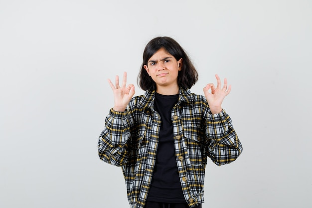 Portret nastoletniej dziewczyny pokazujący ok gest w casualowej koszuli i patrzący niezdecydowany widok z przodu