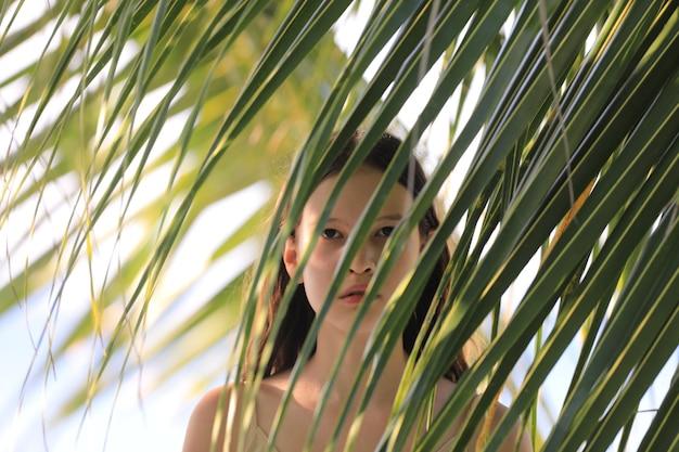 Portret nastoletniej dziewczyny przy palmie