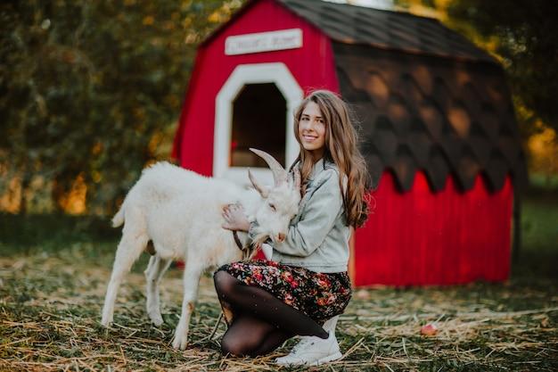 Portret nastoletniej dziewczyny przytulenie z białą kózką w gospodarstwie rolnym. skopiuj miejsce