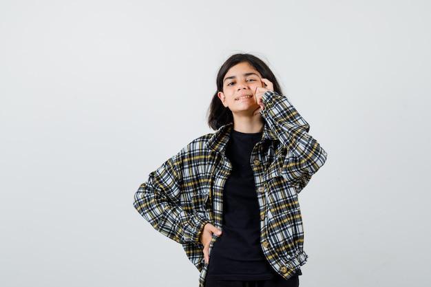 Portret nastoletniej dziewczyny trzymającej palec na skroniach, trzymającej rękę w talii w luźnej koszuli i patrzącej wesoło na widok z przodu