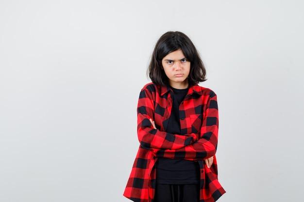 Portret nastoletniej dziewczyny trzymającej ręce złożone w casualowej koszuli i wyglądającej na zrzędliwy widok z przodu