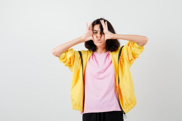 Portret nastoletniej dziewczyny trzymającej się za ręce po obu stronach twarzy w koszulce, kurtce i patrzącej na zirytowany widok z przodu