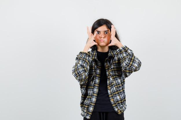 Portret nastoletniej dziewczyny trzymającej się za ręce w pobliżu twarzy, dmuchającej w policzki w luźnej koszuli i patrzącej na ciekawy widok z przodu