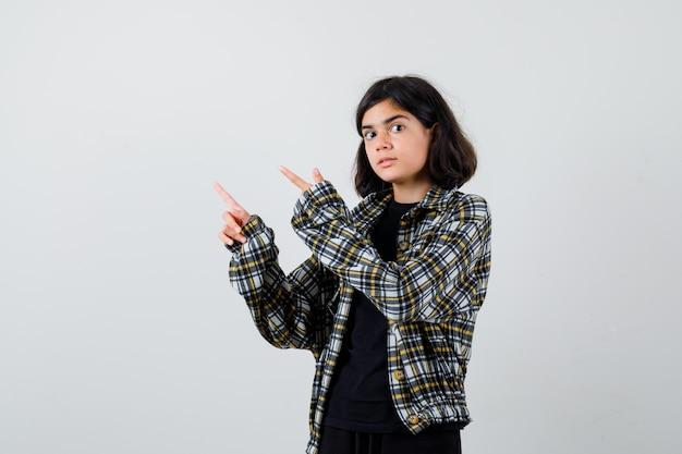 Portret nastoletniej dziewczyny wskazującej na lewy górny róg w casualowej koszuli i patrzącej zszokowany widok z przodu