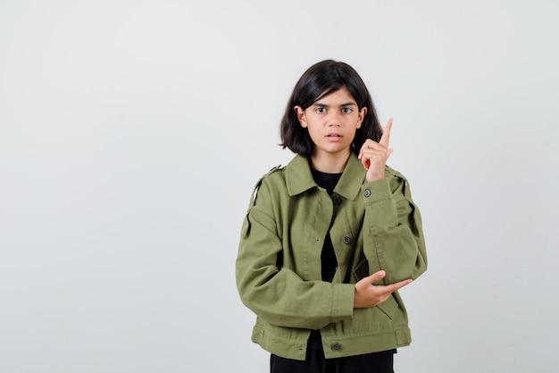 Portret nastoletniej dziewczyny wskazującej w górę w zielonej kurtce i patrzącej na elegancki widok z przodu