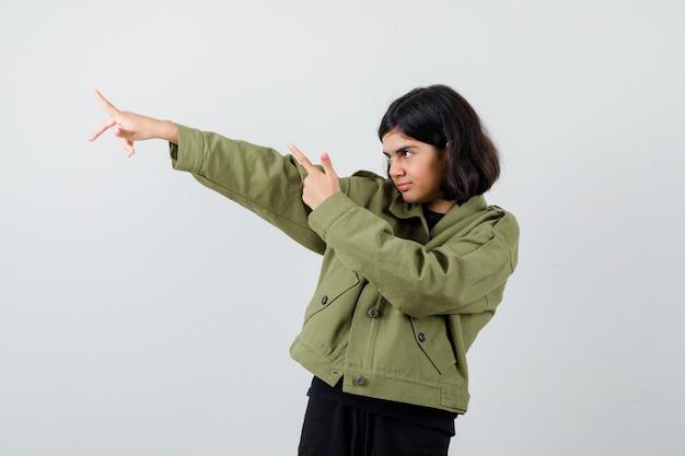 Portret nastoletniej dziewczyny wskazującej w zielonej kurtce i patrzącej pewnie z przodu