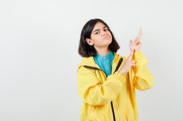 Portret nastoletniej dziewczyny wskazujący w górę w żółtej kurtce i patrzący pewny siebie widok z przodu