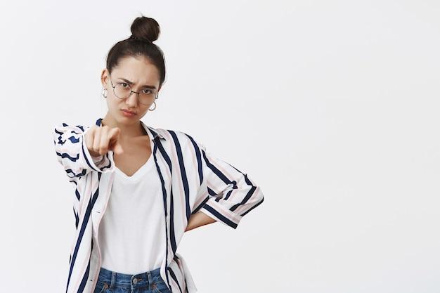 Portret nastrojowej niezadowolonej atrakcyjnej modelki w koszuli i okularach, wskazując, trzymając rękę na biodrze i marszcząc brwi z rozczarowania