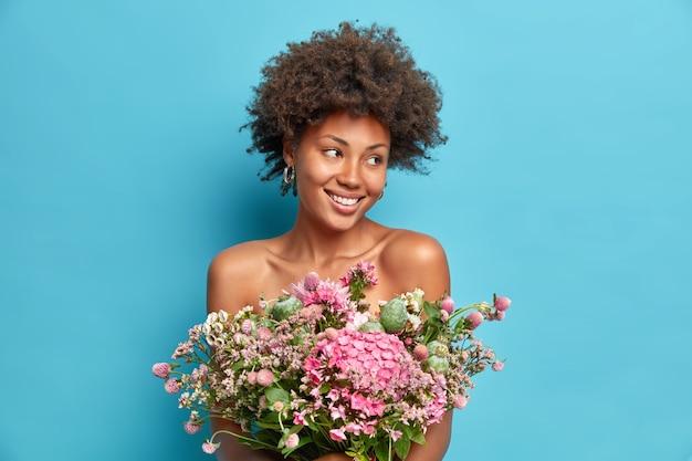 Portret naturalnej młodej kobiety wygląda na bok z radością uśmiecha się delikatnie trzyma piękną tunikę na nagim ciele pozuje z gołymi ramionami odizolowanymi