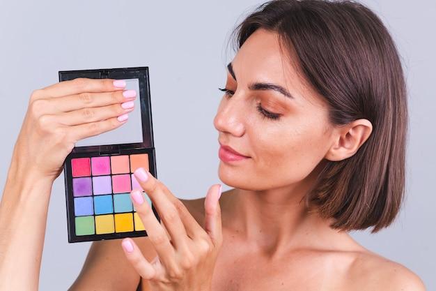 Portret naturalnej urody kobiety trzymaj jasną paletę kolorów wiosenno-letnich cieni do powiek na szarej ścianie