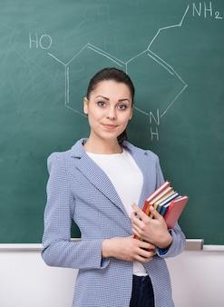 Portret nauczyciela przy tablicy w klasie.