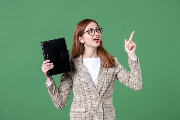 Portret nauczycielki trzymającej notatnik na zielono