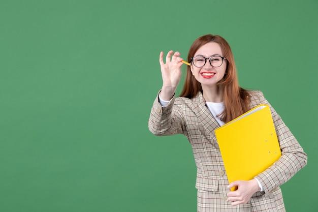Portret nauczycielki trzymającej żółty dokument i ołówek na zielono
