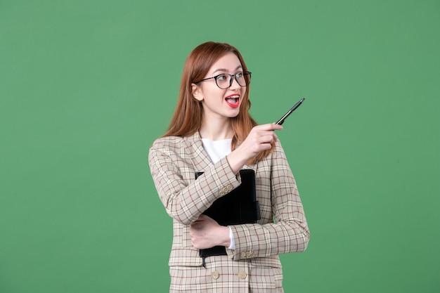 Portret nauczycielki w garniturze z notatnikiem na zielono