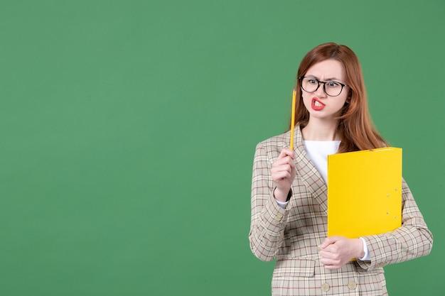 Portret nauczycielki z żółtym dokumentem na zielono