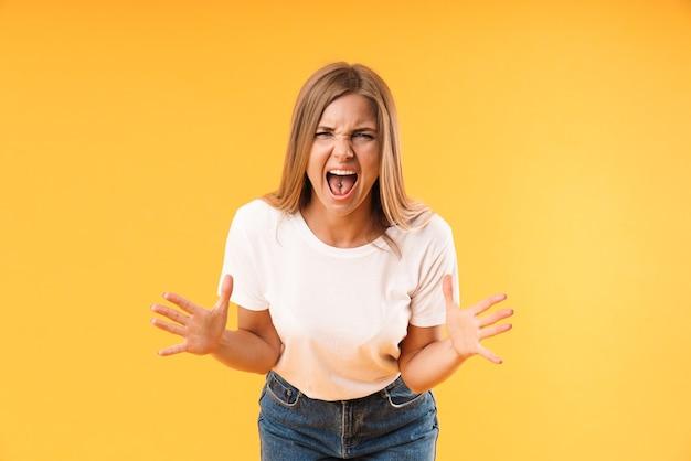 Portret negatywnej zestresowanej kobiety noszącej zwykłą koszulkę krzyczącą i gestykulującą z przodu na białym tle nad żółtą ścianą w studio