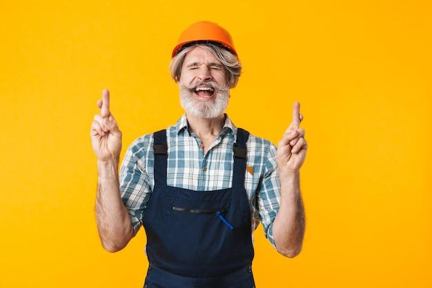 Portret nerwowego starszego konstruktora siwy brodaty mężczyzna w kasku pozowanie na białym tle nad żółtą ścianą pokazując proszę pełen nadziei gest z skrzyżowanymi palcami.