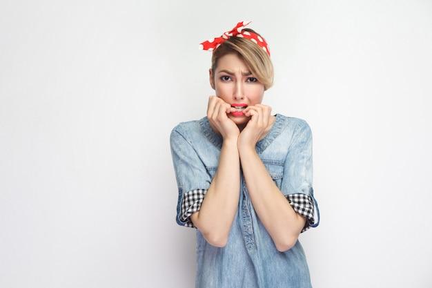 Portret nerwowej pięknej młodej kobiety w dorywczo niebieskiej dżinsowej koszuli z makijażem i czerwoną opaską stojącą, patrząc na kamery i gryząc jej paznokcie. kryty strzał studio, na białym tle.