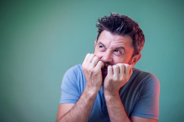 Portret nerwowy mężczyzna gryzie paznokcie