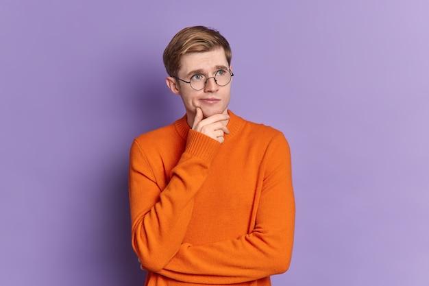 Portret niebieskooki facet zastanawia się nad czymś, co stoi w zamyślonej pozie, trzyma podbródek skoncentrowany w oddali, nosi swobodny pomarańczowy sweter
