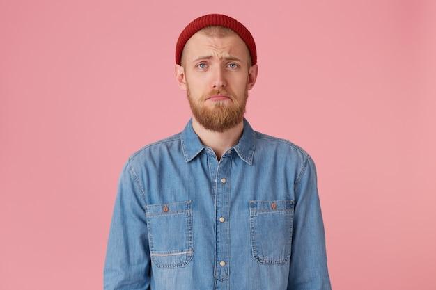 Portret niebieskookiego młodego faceta w czerwonym kapeluszu z czerwoną brodą wygląda na smutnego, zdenerwowanego, sfrustrowanego, niezadowolonego z czegoś, wydyma usta, wyraża zniewagę, nosi modną dżinsową koszulę, na białym tle