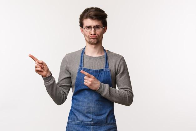 Portret niechętnego i ponurego młodego faceta pracującego w kawiarni się nudzi, nienawidzę czystych stolików po tym, jak klienci wskazują na coś nieprzyjemnego, grymas przeszkadza pokaż lewy baner