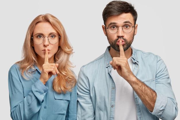 Portret niemej ładnej młodej kobiety i mężczyzny robi znak ciszy, prosi o ciszę, trzyma przednie palce na ustach, stoi blisko, odizolowany na białej ścianie. koncepcja ludzi, spisku i tajemnicy