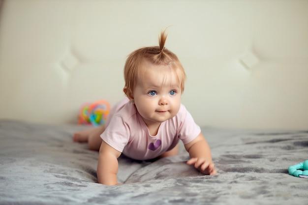 Portret niemowlaka dziecko bawiące się na łóżku