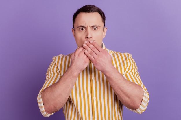 Portret niemy zszokowany facet ręce zakrywają usta wyglądające na aparat na fioletowym tle
