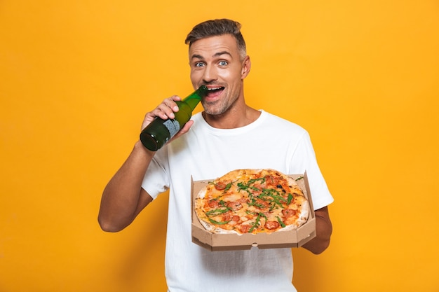 Portret nieogolonego mężczyzny w wieku 30 lat w białej koszulce, pijącego piwo i jedzącego pizzę, stojąc na żółto