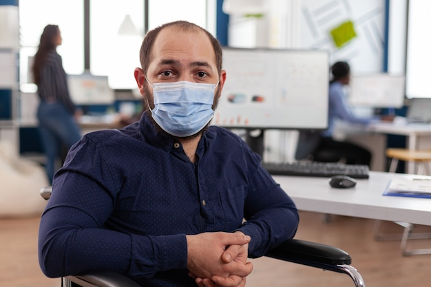 Portret niepełnosprawnego biznesmena noszącego medyczną ochronną maskę na twarz