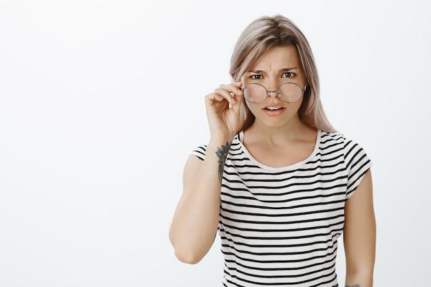 Portret niepewna blondynka w okularach pozowanie w studio