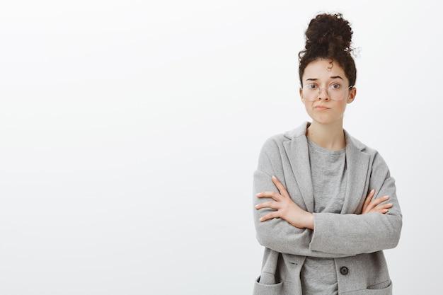 Portret niepewnej wątpliwej uroczej odnoszącej sukcesy kobiety z kręconymi włosami zaczesanymi w kok w szarym płaszczu i okularach, dąsającej się i trzymającej ręce skrzyżowane na piersi