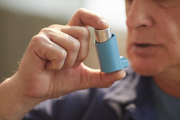 Portret nierozpoznawalnego starszego mężczyzny używającego inhalatora na astmę lub problemy z oddychaniem we wnętrzu domu