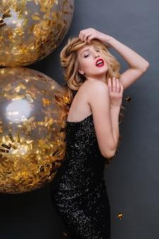 Portret niesamowita młoda kobieta w czarnej luksusowej sukience, z długimi kręconymi blond włosami, czerwonymi ustami. uroczystość, pasja, wspaniały model.