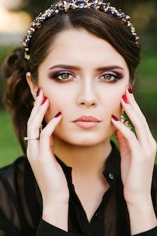 Portret niesamowitej dziewczyny patrząc w kamerę. jasny kolorowy makijaż wieczorowy, biżuteria z kamieniami szlachetnymi, kolczyki, bransoletka. ubrana w czarny strój, czerwony manicure. makijaż w odcieniach fioletu.