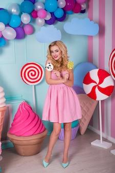 Portret niesamowitej kobiety o słodkich zębach w różowej sukience z cukierkami