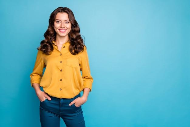 Portret niesamowitej kręconej kobiety biznesu trzymaj się za ręce w kieszeniach ząb uśmiechnięty uśmiechnięty najlepszy naczelnik noszą żółte spodnie koszuli.