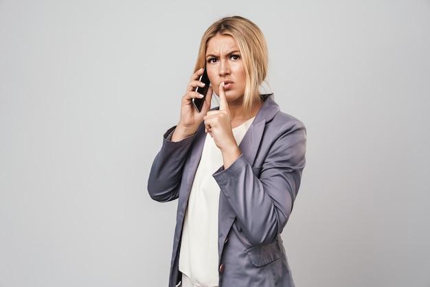 Portret niesamowitej poważnej młodej ładnej kobiety pozującej na białym tle nad szarą ścianą rozmawiającą przez telefon komórkowy