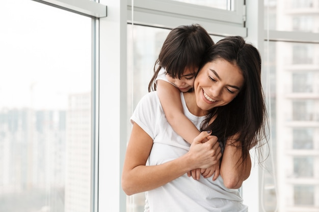 Portret niesamowitej rodziny matki i córki wyrażającej miłość i czułość, jednocześnie przytulający się w domu w pobliżu dużych okien