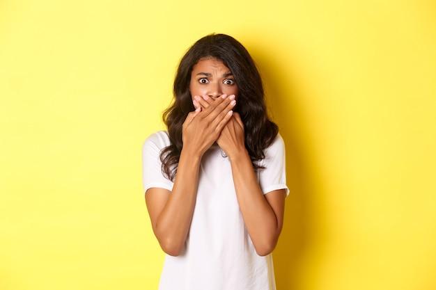 Portret nieśmiałej i przestraszonej afro-amerykańskiej dziewczyny, zamknięte usta i patrząc niespokojnie, stojąc przestraszony na żółtym tle.
