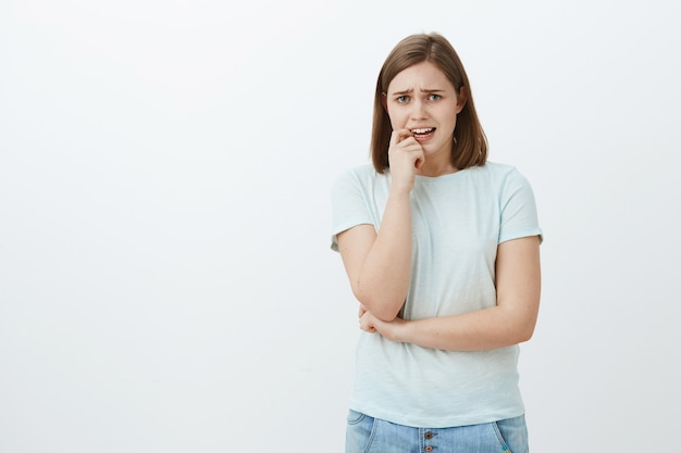 Portret niespokojnej, nieśmiałej kobiety w swobodnym stroju marszczącej brwi, jęczącej i gryzącej paznokieć z nerwowych uczuć, stojącej niepewnie i zmartwionej nad szarą ścianą
