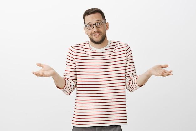 Portret nieświadomego, nieświadomego, przystojnego faceta w okularach, wzruszającego ramionami z rozłożonymi dłońmi i niezręcznym wyrazem twarzy, zdezorientowanego i przesłuchanego, nie mającego pojęcia o pytaniu nad szarą ścianą