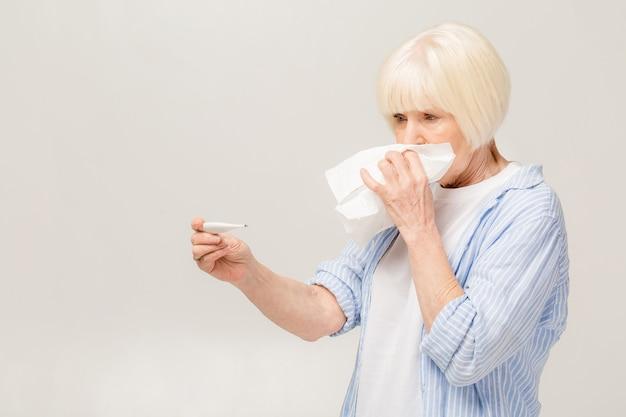 Portret nieszczęśliwa, chora stara kobieta z alergią, przeziębienie, dmuchanie nosa bibułką, na białym tle. wyrazy twarzy ludzkiej. sezon grypowy, szczepienia, profilaktyka, infekcja