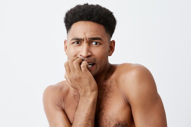 Portret nieszczęśliwego ciemnoskórego afrykańskiego mężczyzny z kręconymi włosami i nagim ciałem trzymającym rękę blisko ust, patrząc na bok z poczuciem winy i zestresowanej twarzy.